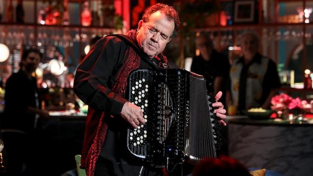Il joue de l'accordéon, les yeux fermés et concentré sur sa musique.