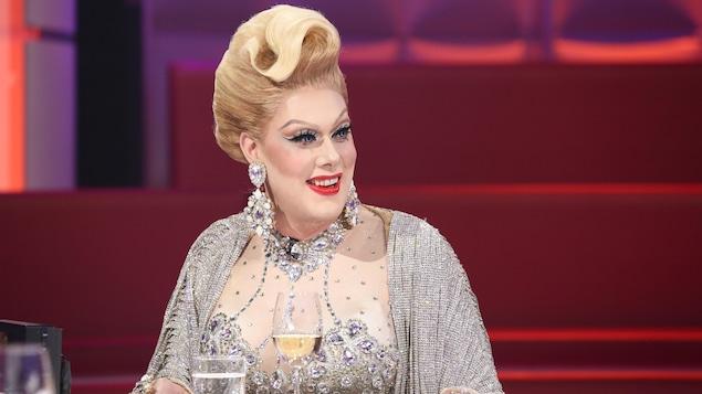 Une drag queen qui porte une perruque blonde et une robe parsemée de pierres brillantes.