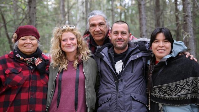 Cinq personnes s'enlacent dans la forêt.