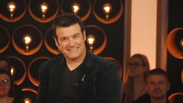 Roch Voisine sourit. Il porte un veston sombre.