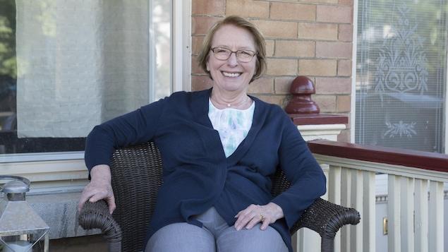 Le personnage de Rollande Mathieu, interprété par Marie-Ginette Guay, est assis sur une chaise devant sa maison et sourit à la caméra.