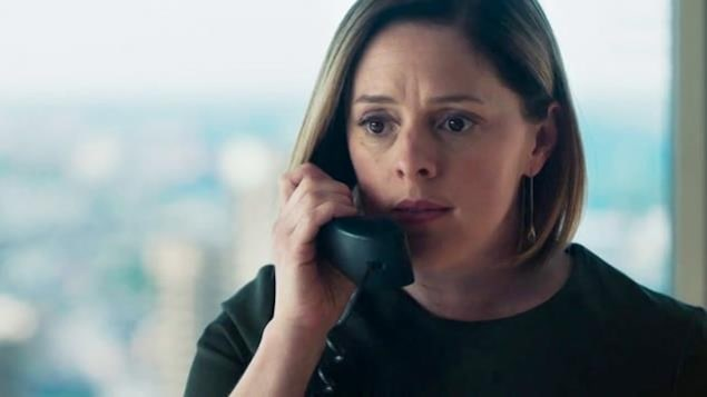 Elle affiche un air sérieux, le combiné du téléphone à l'oreille.