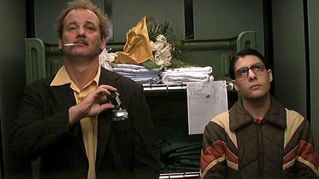 Un homme débraillé, une cigarette aux lèvres et un autre, plus jeune, à ses côtés, en manteau de neige brun.