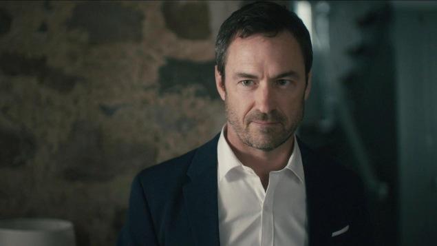 Dans un sous sol avec des murs en pierre, il porte un veston et une cravate.