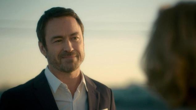 Il porte un veston et regarde une femme avec un regard gentil.