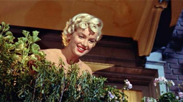 Une jeune femme blonde, aux épaules nues, sur un balcon, derrière des plantes.