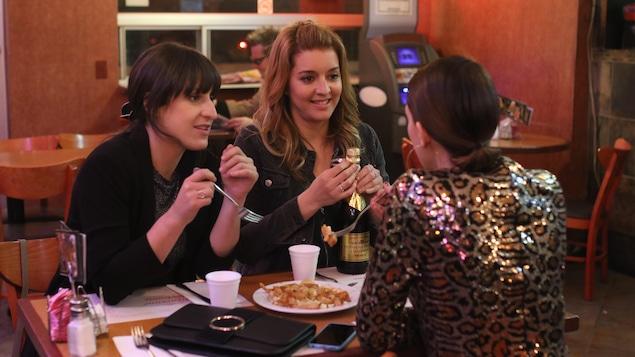 Trois femmes discutent autour d'une poutine au restaurant.