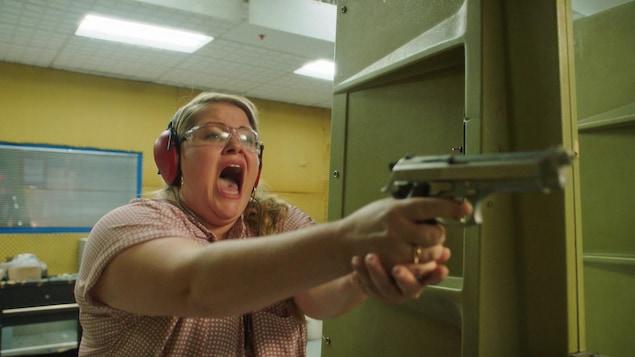 Une femme tient un fusil en criant dans un centre de tir.