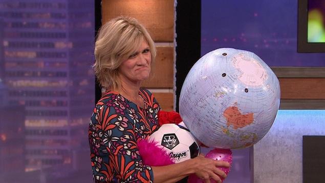 Elle fait l;a moue et tient plusieurs ballons gonflés dans ses bras.