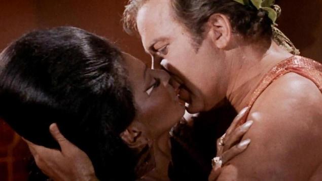 Un homme blanc et une femme noire échange un baiser