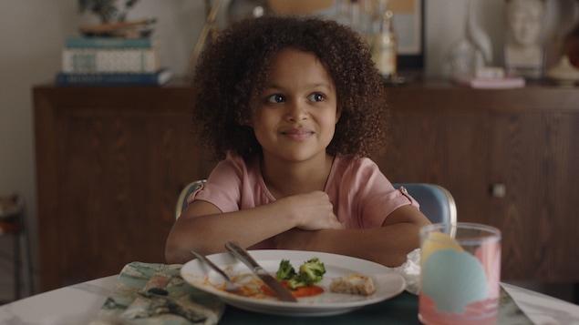 Une petite fille devant un plat à table.