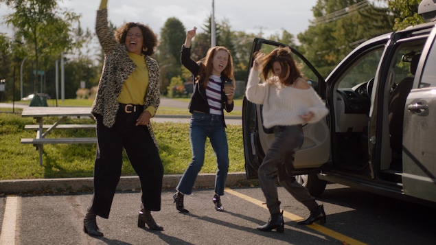 Trois femmes dans un stationnement dansent de joie un poing dans les airs.