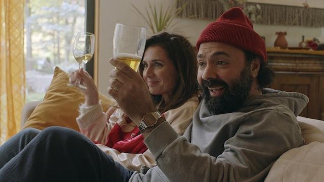 Mélissa Désormeaux-Poulin et Mani Soleymanlou trinquent dans un canapé.