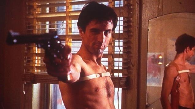Un homme torse nu, devant un miroir, vise avec un revolver.