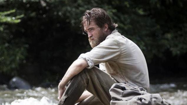 Un explorateur assis sur un radeau devant une rivière