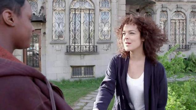 Tina parle avec Edwidge. Elle porte un t-shirt blanc et une veste bleue.