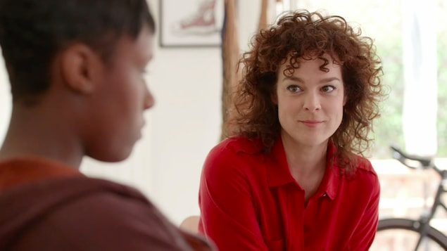 Tina a les cheveux frisés. Elle porte un chandail rouge et elle sourit.