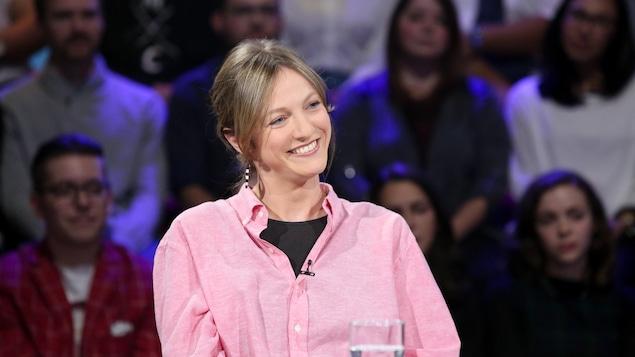 Catherine Dorion, souriante, est assise à la table des invités.
