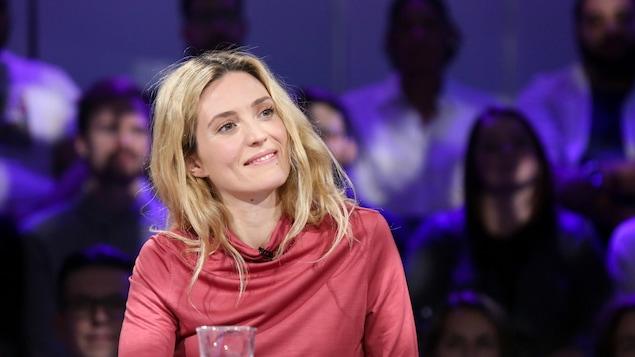Evelyne Brochu, souriante, est assise à la table des invités.