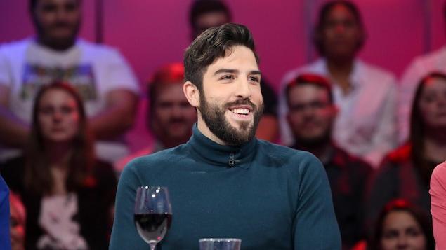Yannick De Martino est assis, souriant, à la table des invités.