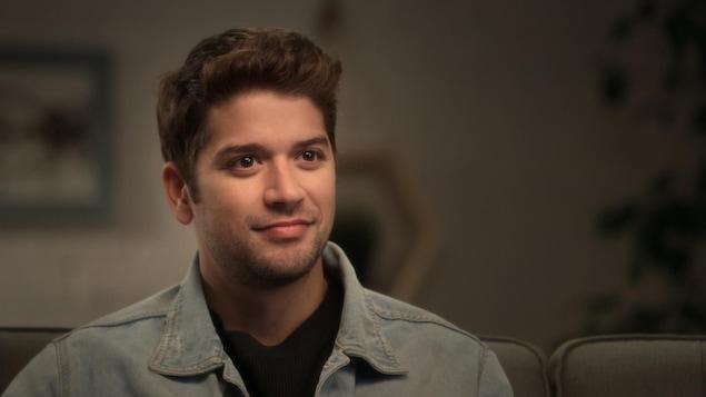 Le jeune acteur porte une veste de denim.