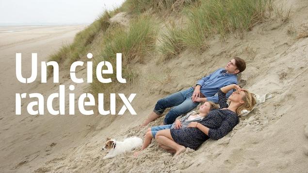 Un homme, une femme et une petite fille allongés sur le sable, le titre Un ciel radieux à leur gauche.