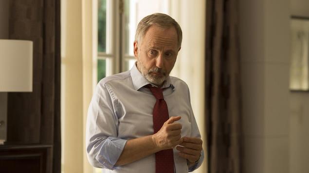 Un (Fabrice Luchini) homme en chemise et cravate, l'air préoccupé.