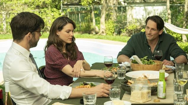 Les trois personnes sont assises à une table à l'extérieur avec de la nourriture et du vin. Les deux hommes se regardent.