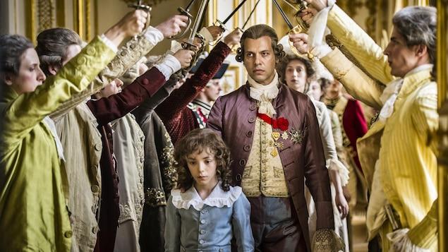 Le roi (joué par Laurent Laffitte) derrière un petit garçon passe sous une haie d'honneur de ses nobles.