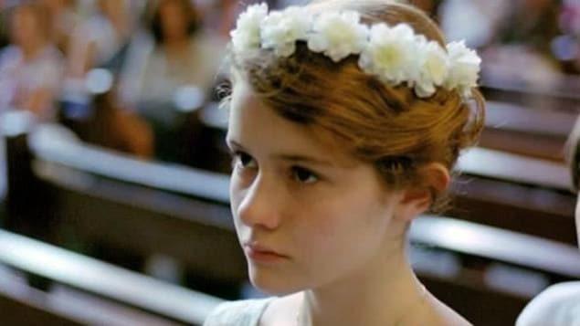 La jeune héroïne, sa couronne de communiante sur la tête