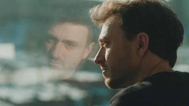 Reflet de Benoit McGinnis qui se regarde à travers une vitre.