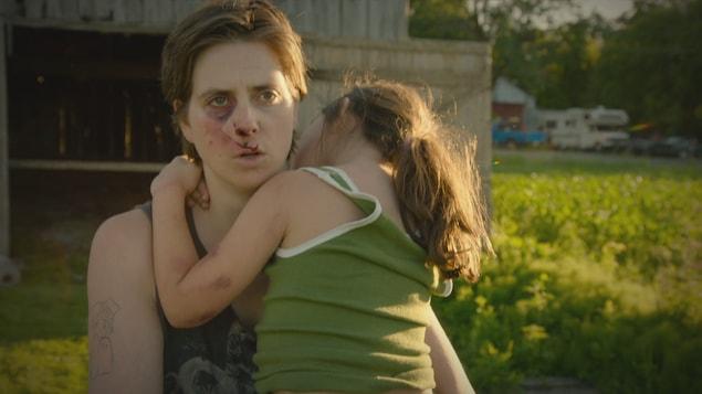 Jeanne Biron tient Jeanne Biron enfant dans ses bras en regardant droit devant elle