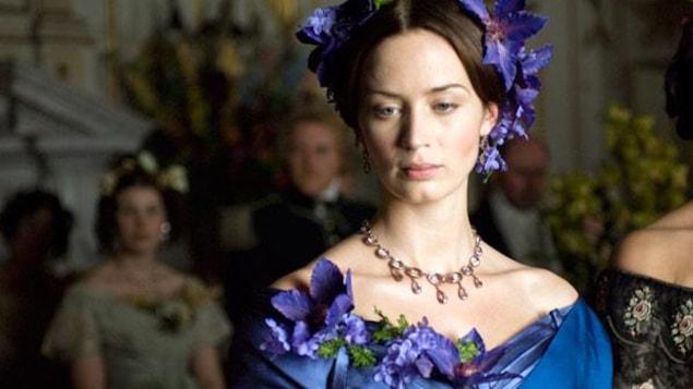 Une femme en robe de bal bleue, une couronne de fleurs sur la tête.