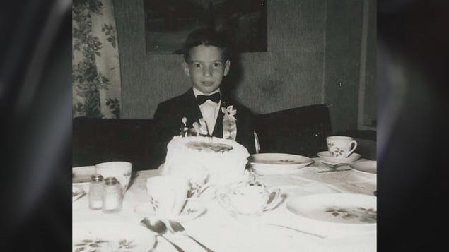 Photo d'archives de Guy Mongrain, enfant, devant son gâteau de première communion dans la salle à manger familiale.
