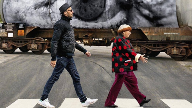 Un homme mince et grand et une femme petite et plus ronde traversent un passage protégé.