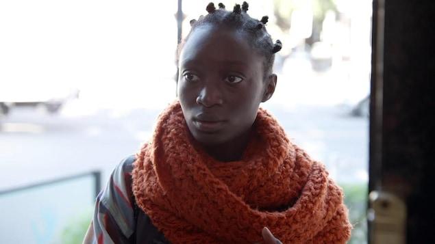 Une jeune femme qui porte un gros foulard orange.
