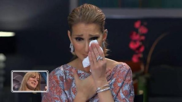 Céline Dion s'essuyant les yeux avec un mouchoir.