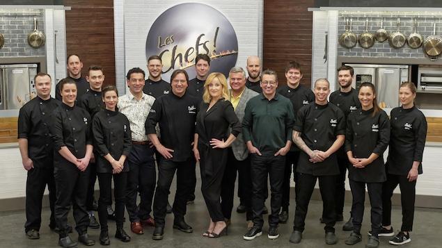 Le groupe pose en cuisine devant le logo de l'émission.