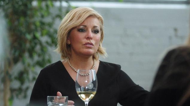 Elle parle à Nathalie Simard, assise à une table de restaurant et devant un verre de vin blanc.