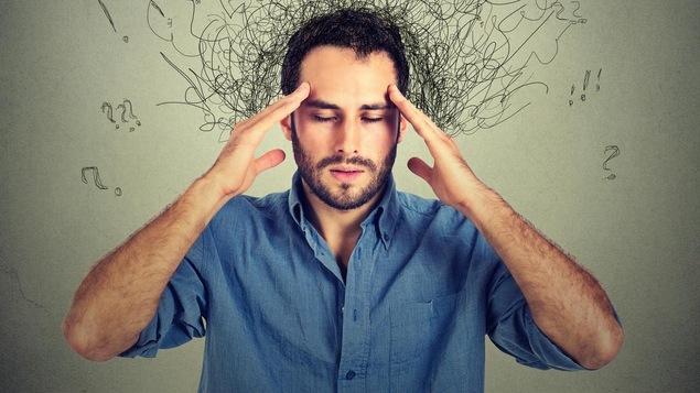 Un homme se tient la tête avec les deux mains. Il y a des illustrations autour de sa fête qui nous aident à comprendre qu'il est stressé.