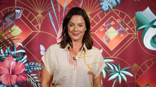 Elle pose en souriant devant le fond coloré, style tapisserie au motif de jungle, de l'émission Bonsoir Bonsoir.