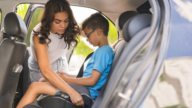 Une mère qui attache son fils dans son siège d'appoint.