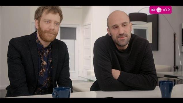 Les deux comédiens sont assis à un comptoir et discutent.