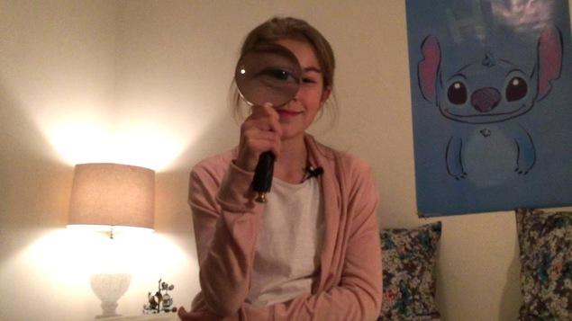 Elle tient une loupe dans ses mains