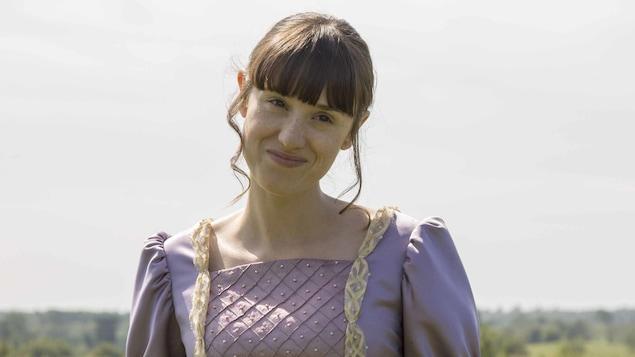 La jeune comédienne pose dans un champs