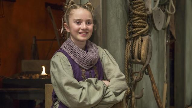 La jeune fille sourit près de la forge