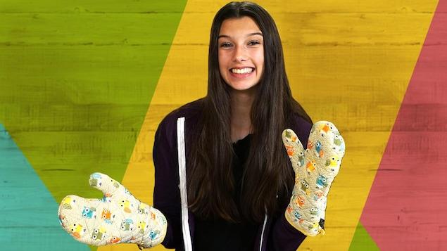 La jeune ado sourit en portant des mitaines de cuisine