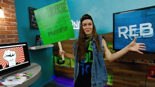 Mélissa Cassista brandit une pancarte où il est écrit : Paix Liberté pas le temps de niaiser! On a une planète à sauver!