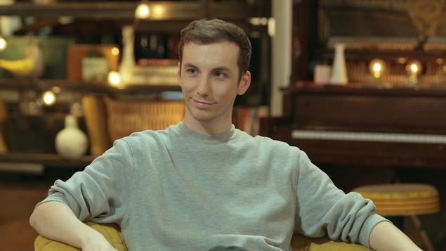 Il est assis sur le plateau télé et sourit.
