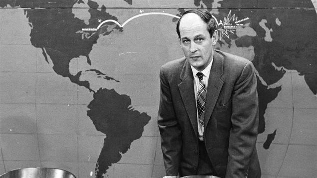 Debout devant une carte du monde, l'animateur de l'émission Point de mire, René Lévesque est appuyé au dossier d'une chaise.